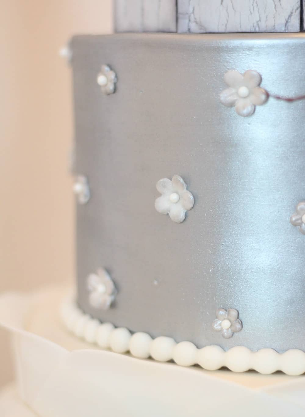 Adding blossoms to silver cake tier
