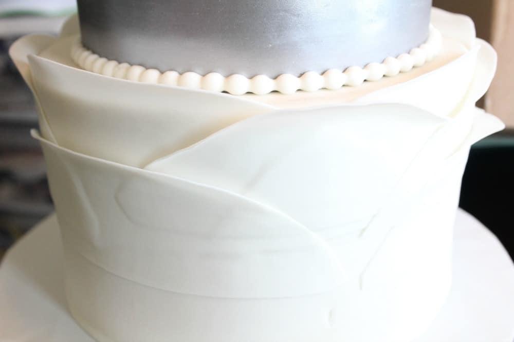 Attaching fondant ruffle petals to cake