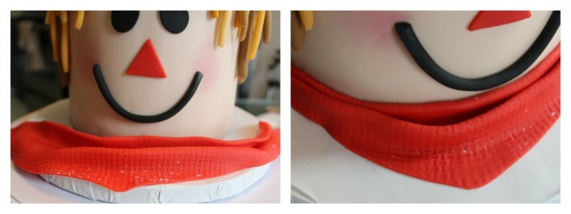 Attaching the fondant bandana to the scarecrow cake