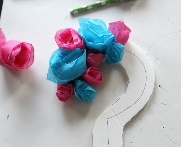 Adding the roses to the question mark cake topper