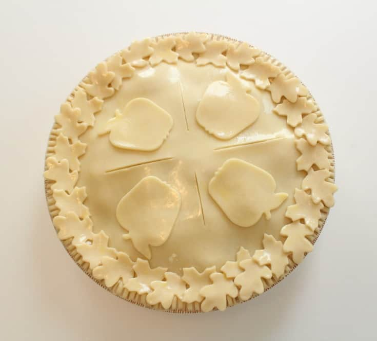 Adding the cut out pie crust shapes to the apple pie