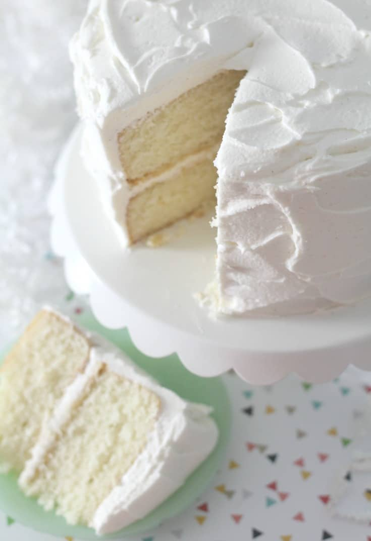 Vanilla cake on white cake stand with slice of cake on small green plate
