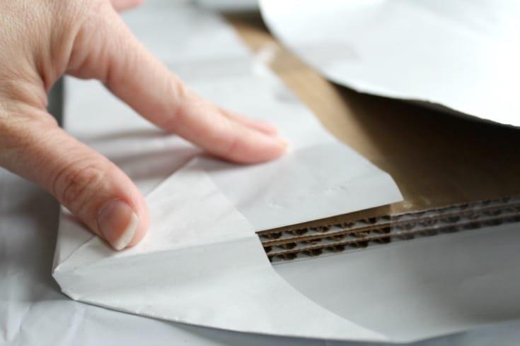 folding back the corners on the cake board