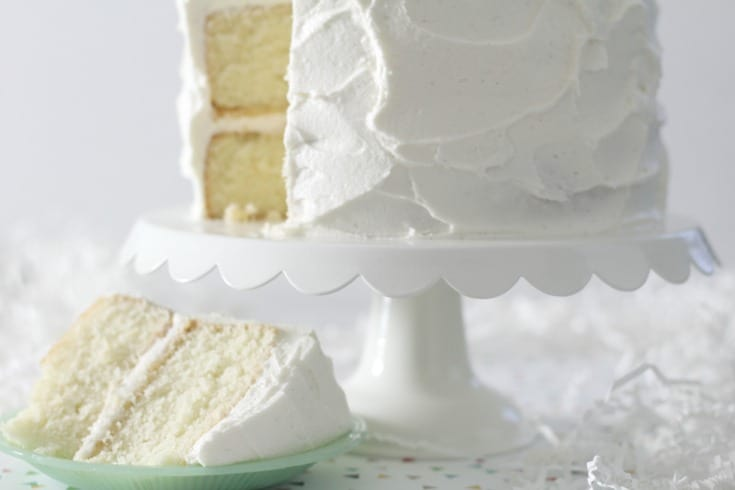 Favorite Vanilla Bean Cake On White Stand With Slice Cut A Small Green Plate