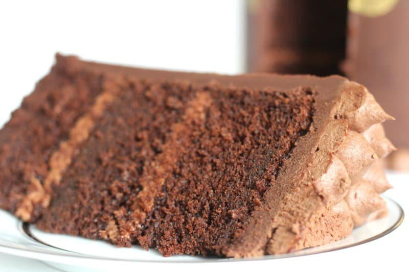 Chocolate Butter Cake slice on white plate with cake in background