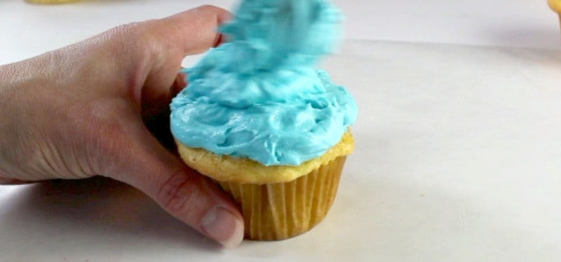 Adding buttercream to cupcake to look like water