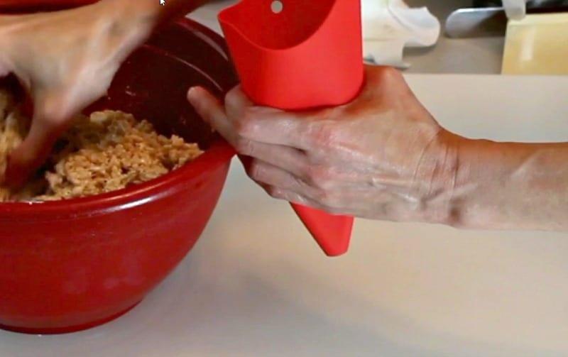Adding rice krispie treats to silicone funnel
