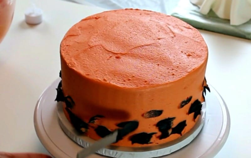 Icing the orange and black buttercream cake