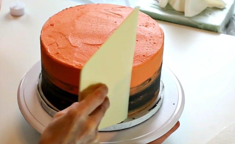 Smoothing the orange and black buttercream cake
