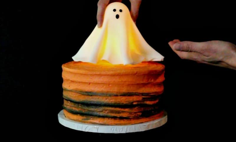 Adding fondant ghost to cake