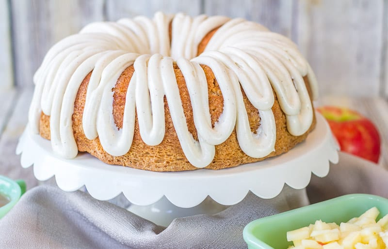 Moist Apple Coconut Cake with Cinnamon Cream Cheese Glaze on a white cake stand