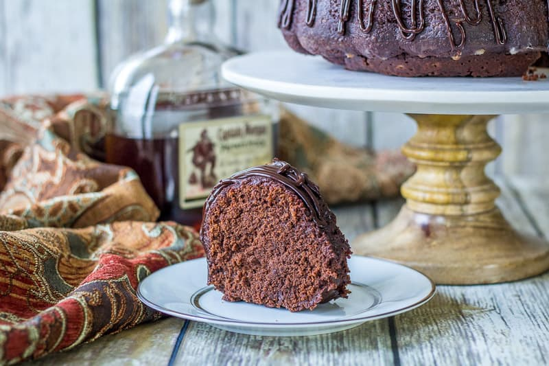 Slice of Chocolate Rum Cake on a white plate with cake in the background