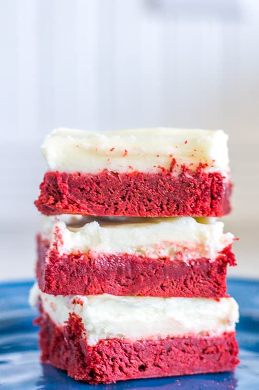 Cream Cheese Buttercream on top of red velvet cake bars on a blue plate