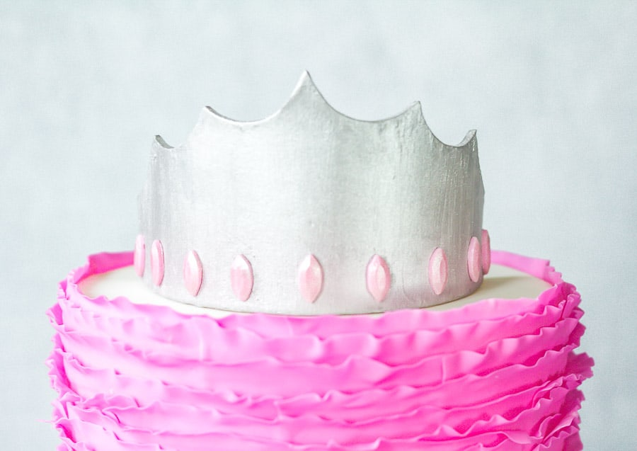 Silver gumpaste crown on top of pink ruffled cake