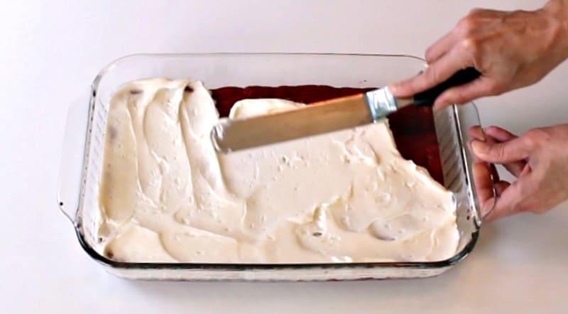 Adding cream cheese buttercream to red velvet cake bars