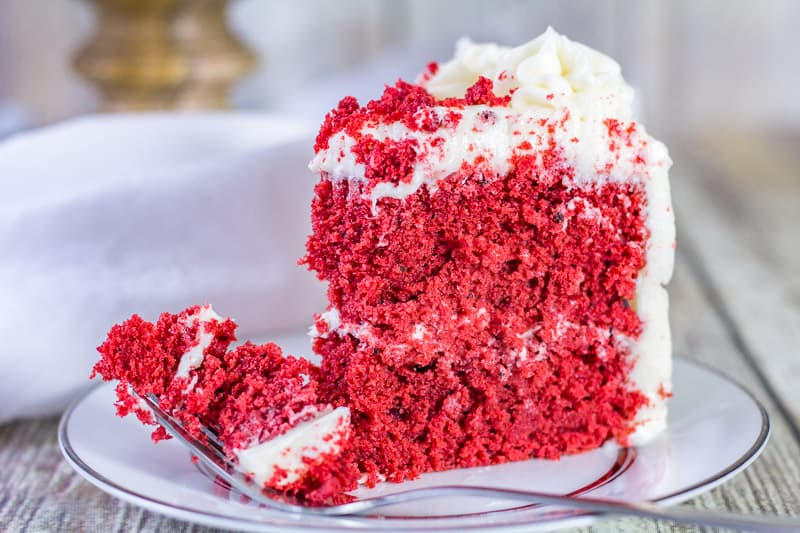 Sour Cream Red Velvet Cake slice on a white plate with a fork