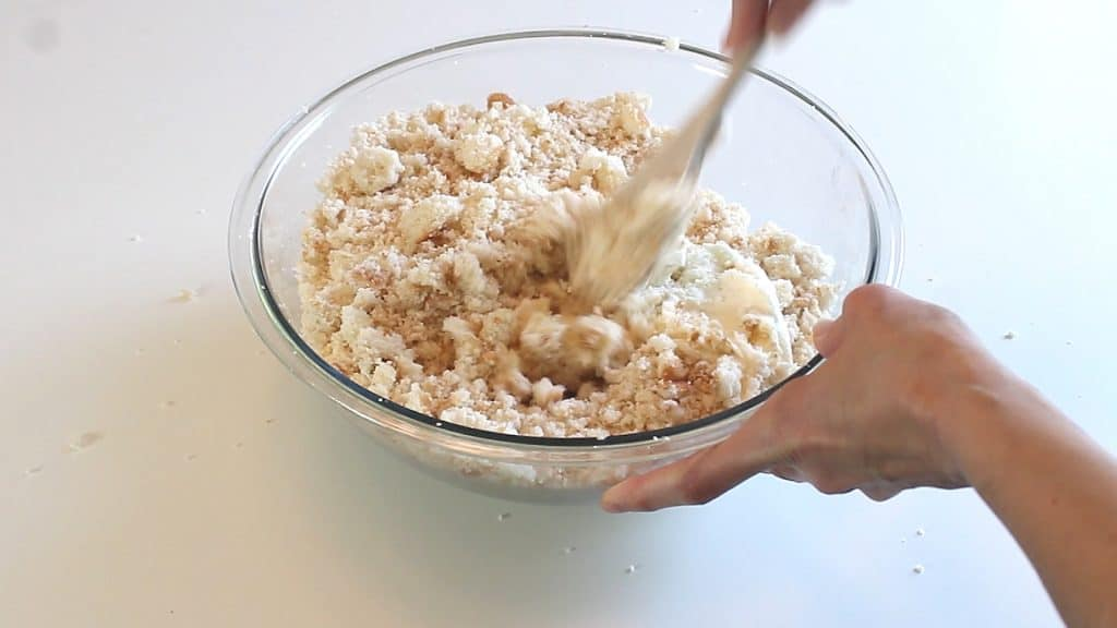 Mixing buttercream into cake crumbles to make cake balls