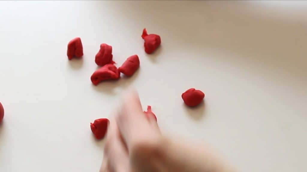 pulling off fondant bits to make the fondant rose petals