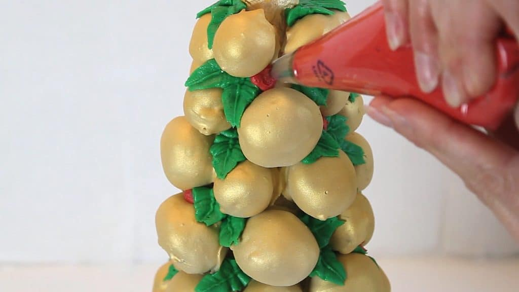 Piping red berries onto the Cake Pop Christmas Tree