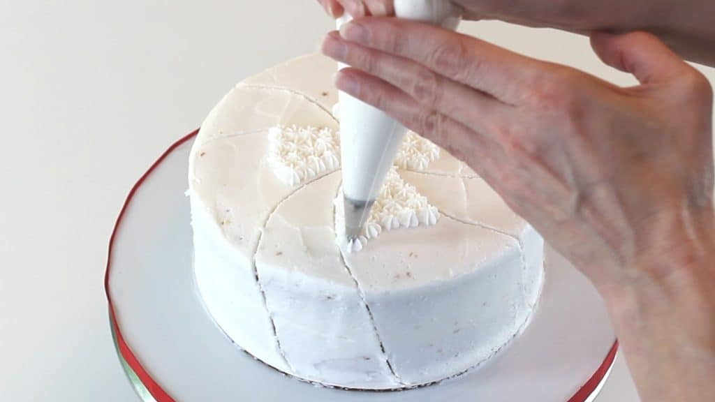 Piping white stars onto cake