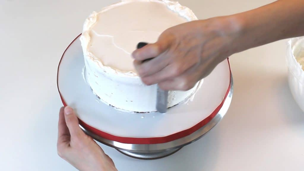 Smoothing sides of buttercream cake