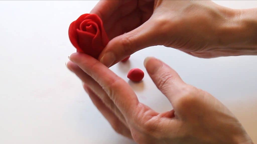 adding fondant rose petal to fondant rose