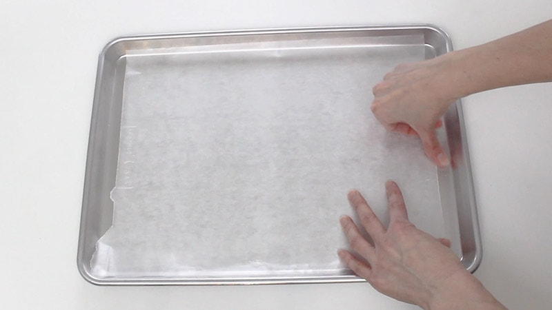 taping wax paper onto cookie sheet