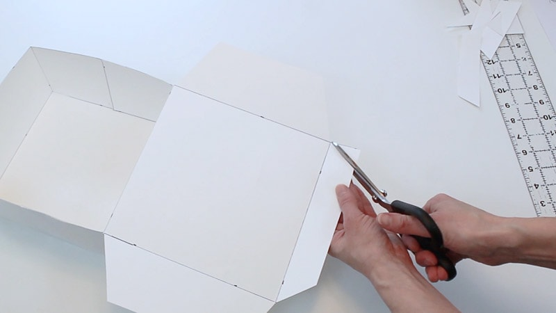 cutting the top flap of the posterboard box