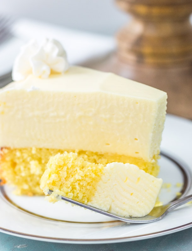 Close up view of cake bottom lemon cheesecake on a plate with a fork