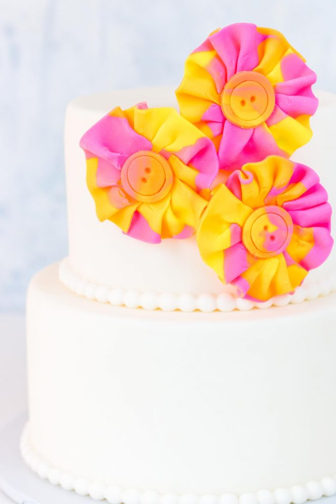 Watercolor fondant fabric look flowers on a two tiered cake