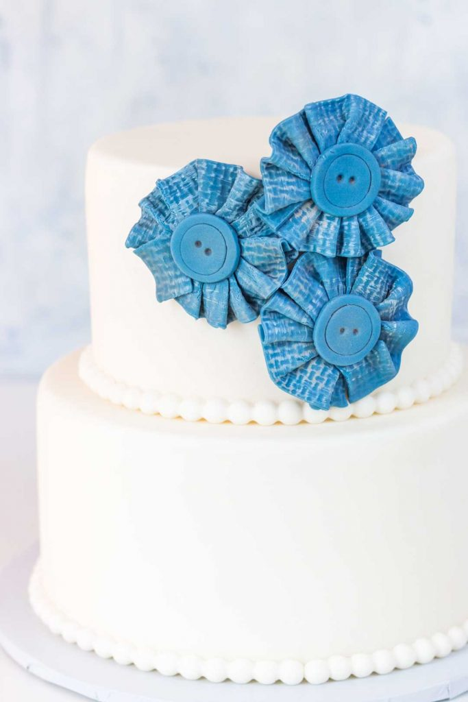 Blue jean fondant fabric look flower on two tiered cake