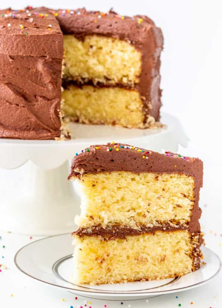 Classic Yellow Cake with Fudge Frosting on a white cake plate