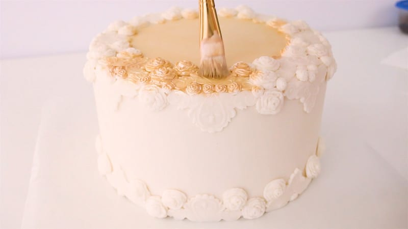 painting luster dust onto cake