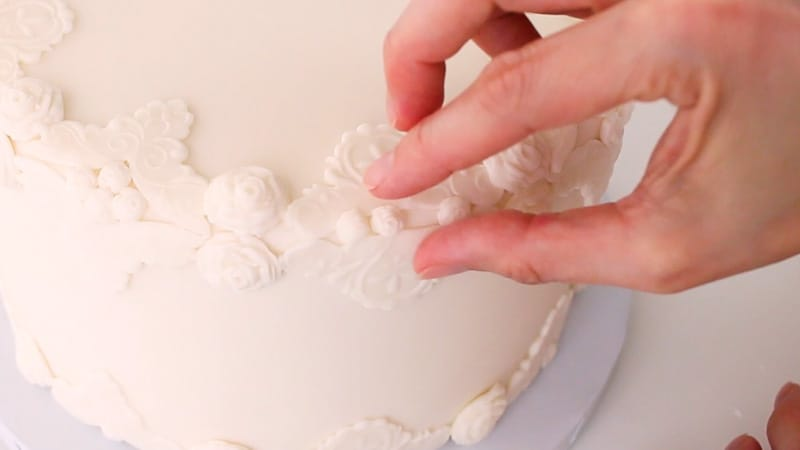 adding fondant roses to bas relief cake