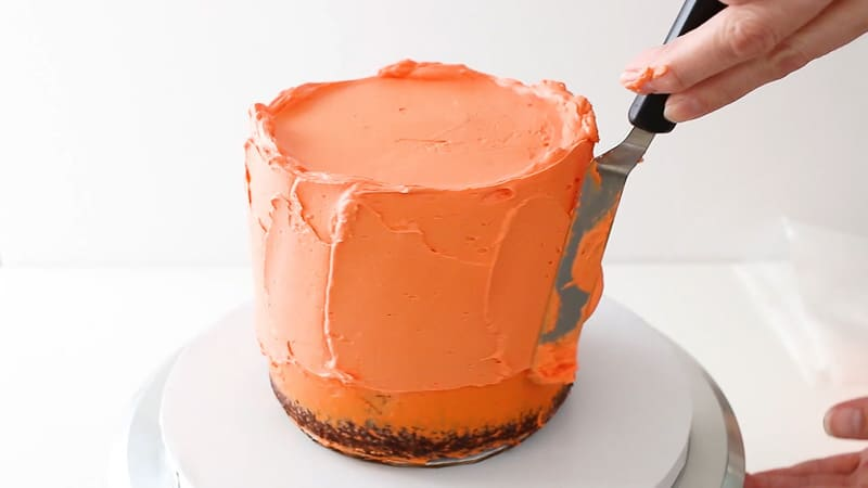 adding a second coat of buttercream to cake