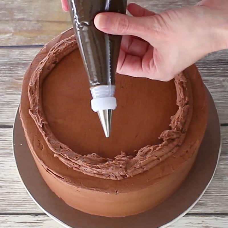 Adding the base of the buttercream wreath onto the cake