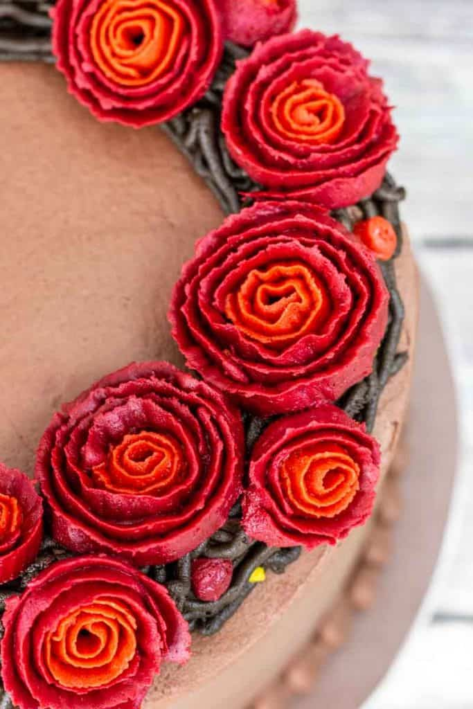 Close up view of red and orange buttercream ribbon roses on cake