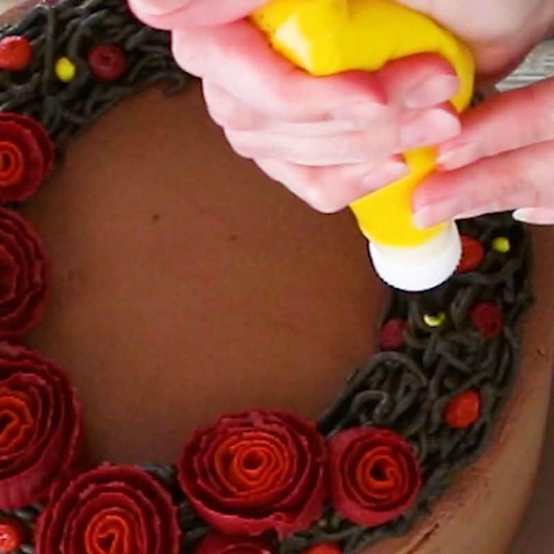 Piping yellow berries on buttercream cake