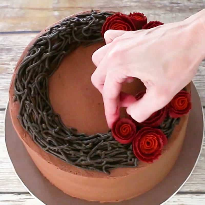Adding buttercream roses to cake