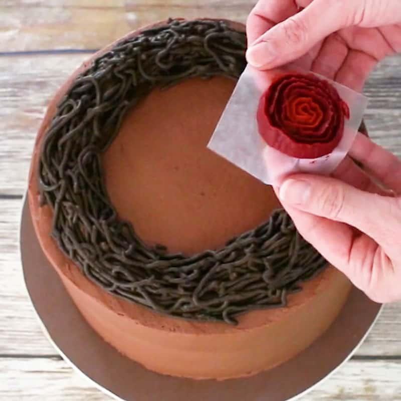 Adding buttercream roses to cake