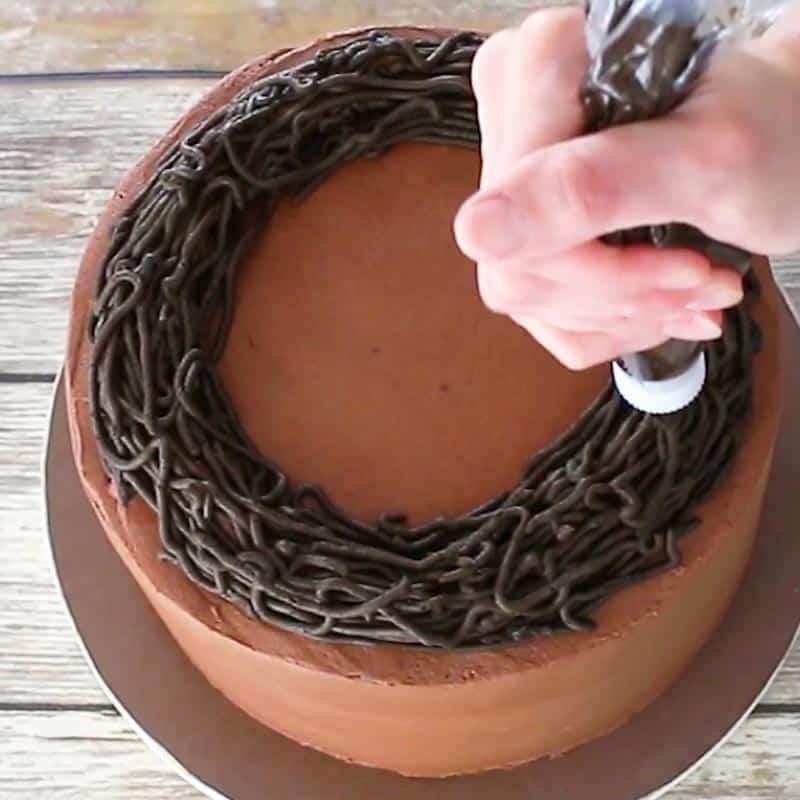Piping a wreath onto a buttercream cake