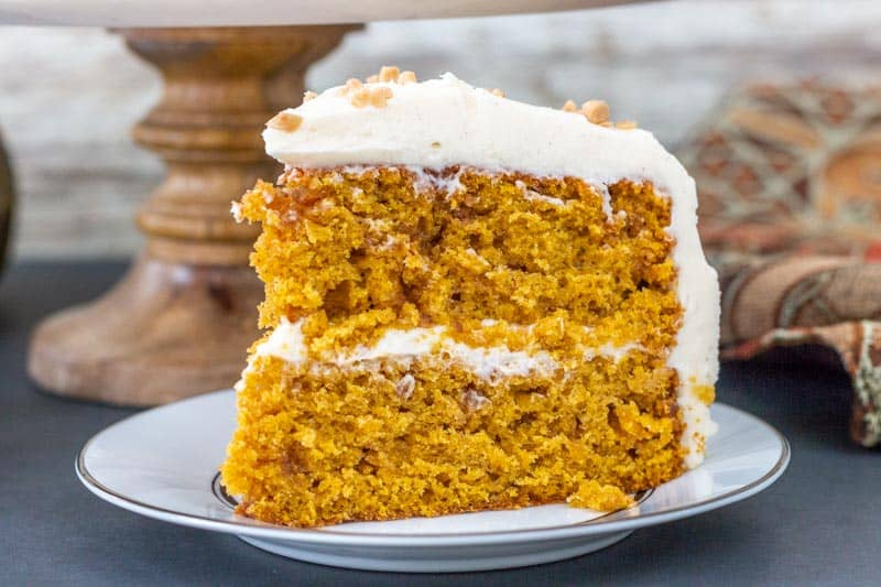 large slice of pumpkin layer cake on a white plate
