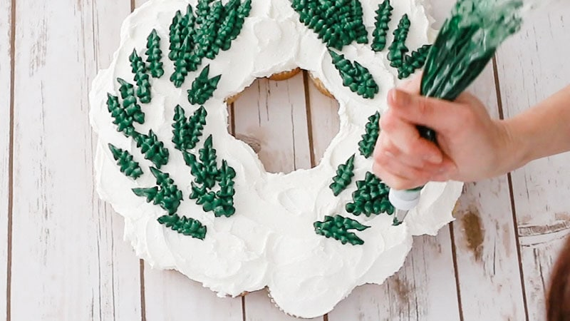 piping leaves onto wreath cake