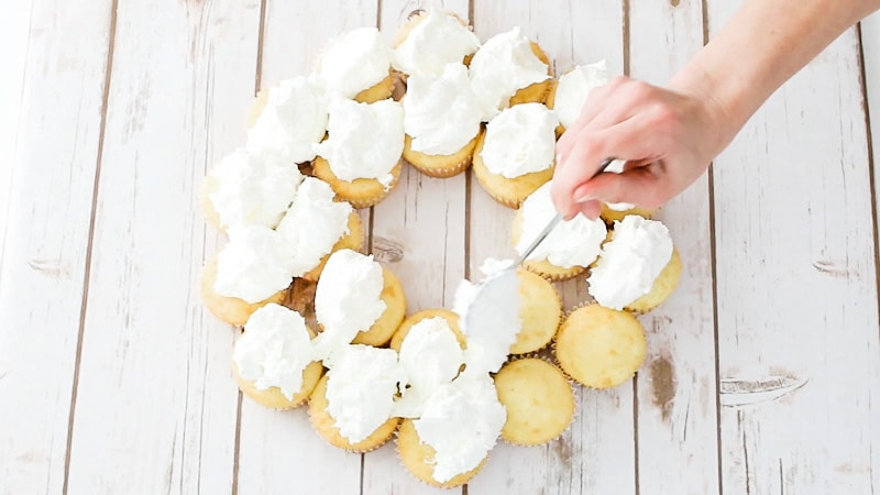 adding buttercream onto cupcake cake