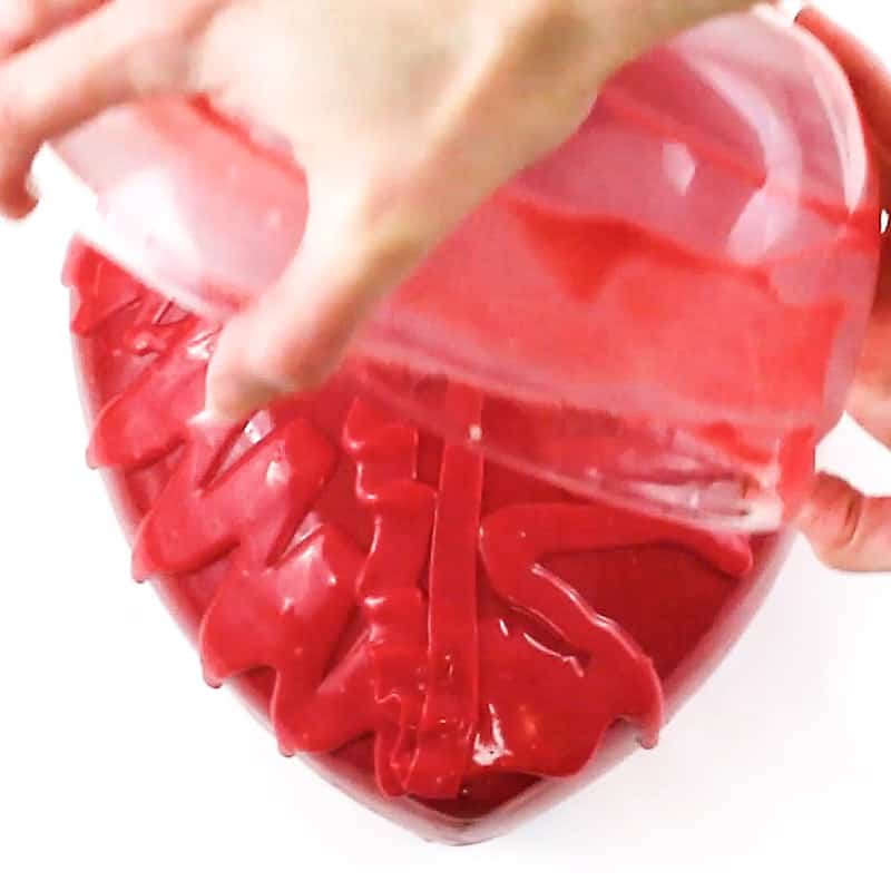 pouring ganache over heart cake