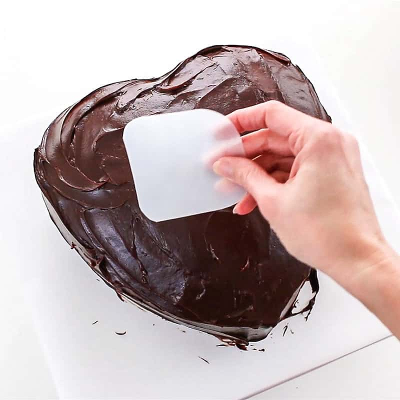 covering the heart cake in ganache