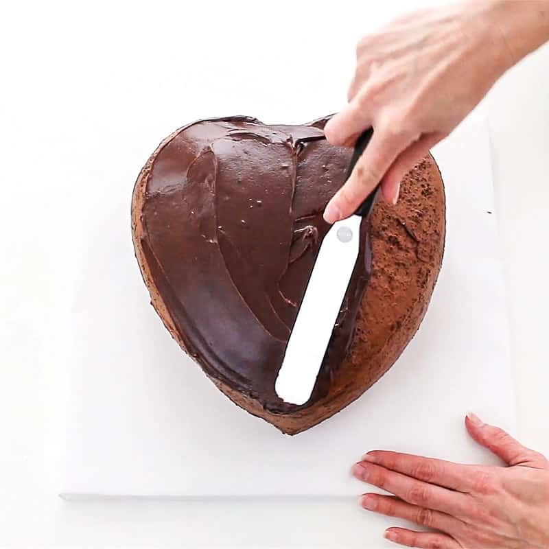 adding ganache to heart cake