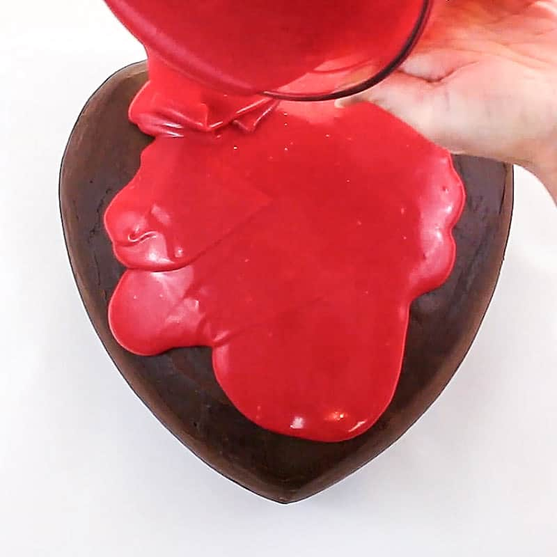 pour red ganache over heart cake