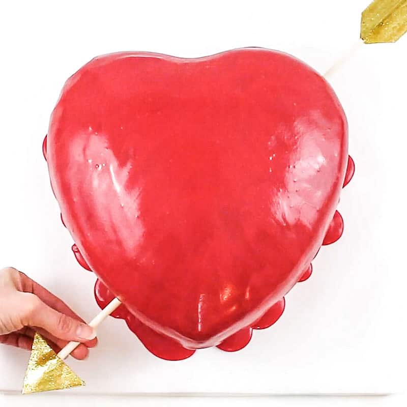 inserting arrow into heart cake