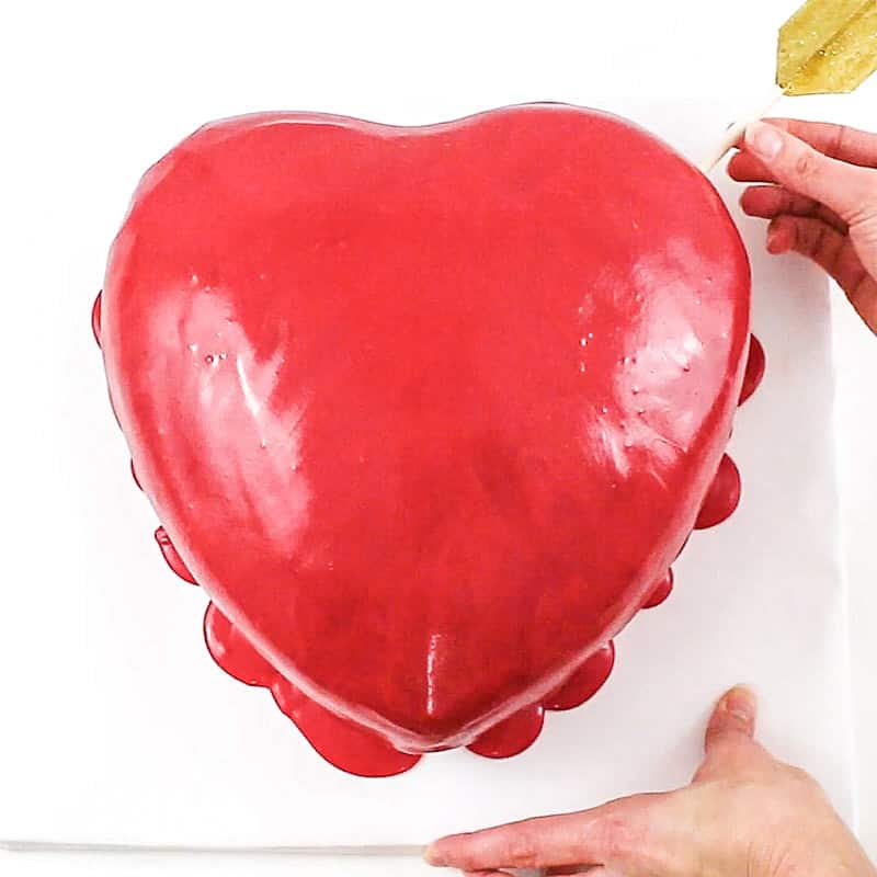 inserting the arrow into the heart cake